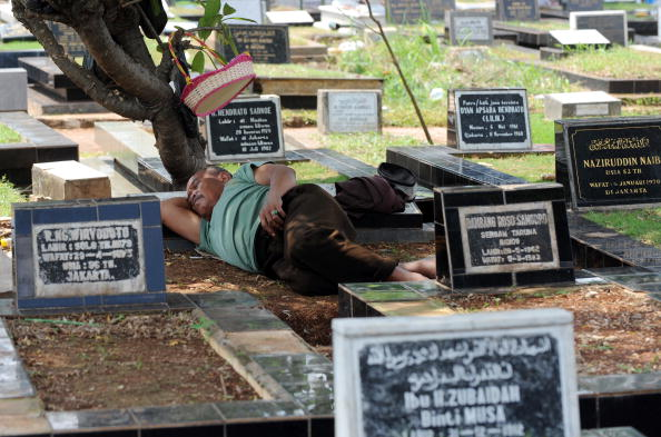 A vendor takes a nap on graves as Indone
