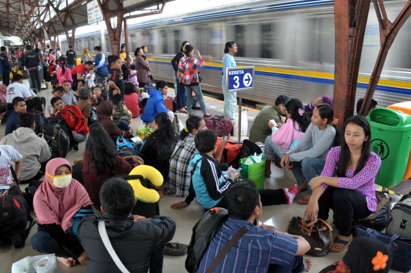 Hundreds of Indonesian wait for the train at a train station to go to other cities in Java island as Indonesians return home to provinces ahead of the Muslim festivities of Eid al-Fitr in Jakarta on July 26, 2014.  Indonesia is the world's most populous Musilm nation.    AFP PHOTO / Bay ISMOYO        (Photo credit should read BAY ISMOYO/AFP/Getty Images)