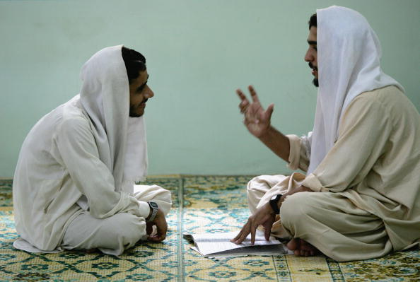 MULTAN, PAKISTAN - AUGUST 04:  Shiite Muslim madrassa students discuss the Arabic alphabet during long hours of Islamic study on August 4, 2005 in Multan, Pakistan.  A million students in Pakistan study at madrassas, which provide free room and board. In addition to Islamic studies, some of the more progressive madrassas in Multan also offer English and computer courses.  (Photo by John Moore/Getty Images)