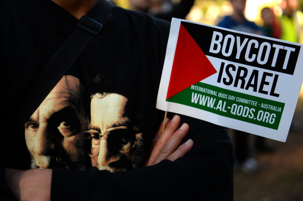 A Demonstrator holds a flag while wearing a t-shirt carrying images of Iranian spritual leader Ayatollah Khomeini (L) and supreme leader Ayatollah Ali Khamenei during a rally to mark Al-Quds day on the last friday of the holy month of Ramadan in Sydney on August 2, 2013. Demonstrators carrying banners and placards marched through the streets in southern Sydney to protest against Israel and prayed for the liberation of Palestine.  AFP PHOTO / Saeed Khan           (Photo credit should read SAEED KHAN/AFP/Getty Images)