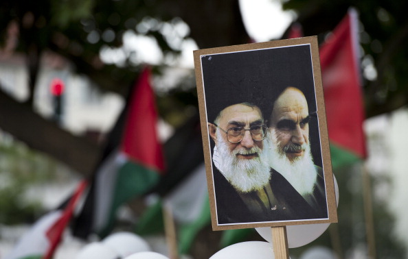 A demonstrator displays a  placard featuring portraits of Iranian supreme leader Ali Khamenei (L) and former supreme leader Ayatollah Khomeini (R) during a Quds Day rally in Berlin August 3, 2013. Quds Day, initiated by the Iranian government in 1979, takes place every year on the last friday of Ramadan, to express solidarity with the Palestinian people and to oppose Israel's control of Jerusalem. AFP PHOTO / JOHN MACDOUGALL        (Photo credit should read JOHN MACDOUGALL/AFP/Getty Images)