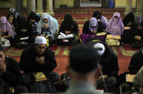 Indonesian Muslim students read from the