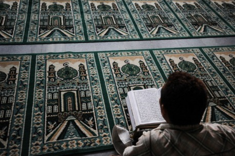SURABAYA, INDONESIA - JULY 13:  A Muslim man reads the Quran as he waits for the breaking of the fast during Ramadan on July 13, 2014 in Surabaya, Indonesia. Ramadan, the ninth month of the Islamic calendar is marked by a month of fasting, prayers, and recitation of the Quran.  (Photo by Robertus Pudyanto/Getty Images)